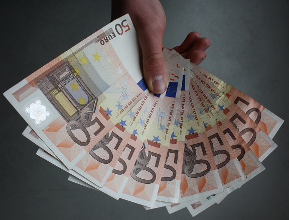 privat Geld leihen um Schulden zu bezahlen Geldscheine Hand hinhalten
