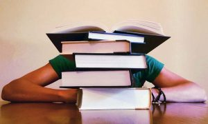 Student hinter Berg aus Büchern